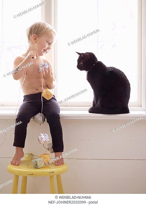Boy and cat sitting on windowsill