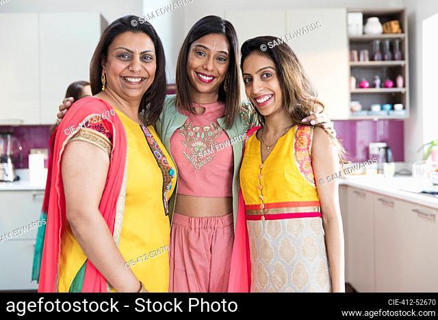 Portrait happy Indian sisters in saris in kitchen