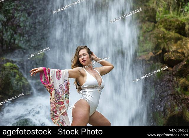 Woman posing in a white bodysuit in front of a waterfall