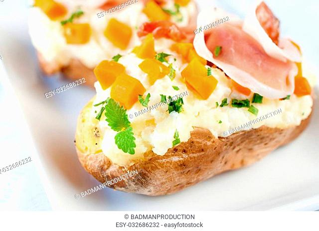 Fresh baked potatoes stuffed with white cheese cream and prosciutto