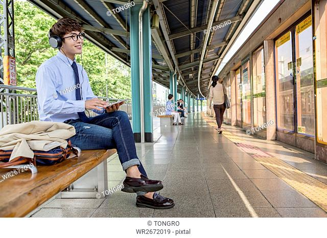 Smiling businessman waiting for train sitting on bench