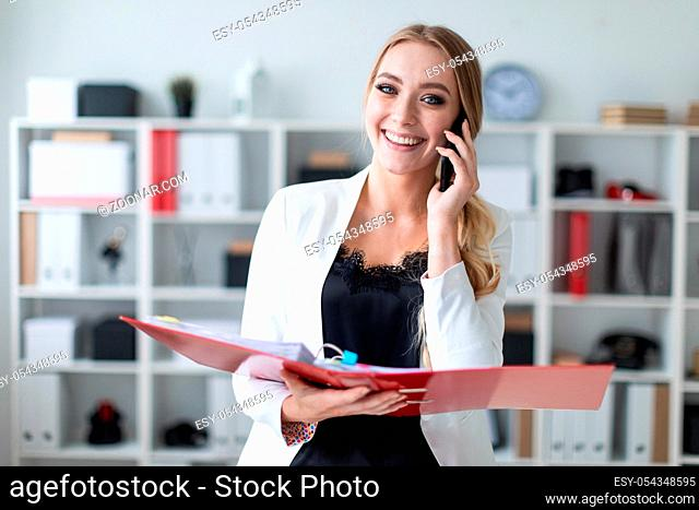 Beautiful young girl with blond hair in a white jacket and black blouse is working in the office. photo with depth of field
