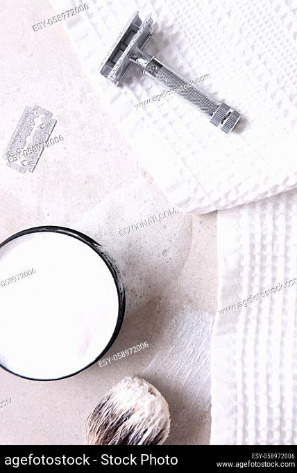 Shaving Still Life: Safety razor with towel, brush and soap and blade on a gray tile surface