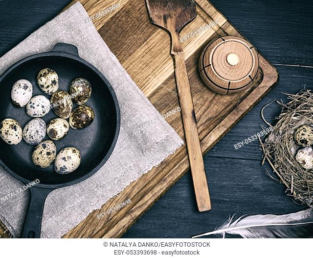 raw quail eggs in a black round frying pan on a brown wooden board, top view