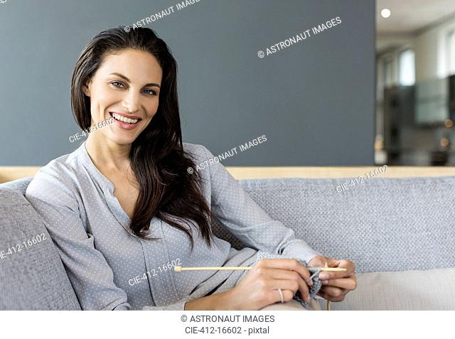 Portrait of smiling woman knitting on sofa