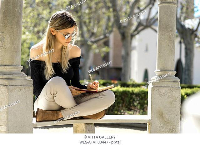 Young woman with notebook sitting on bench writing down something