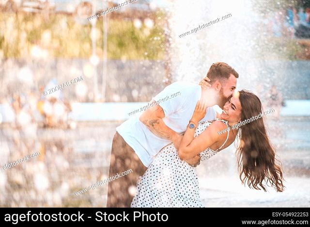 Handsome guy and beautiful girls kissing on the background of a fountain. Love concept