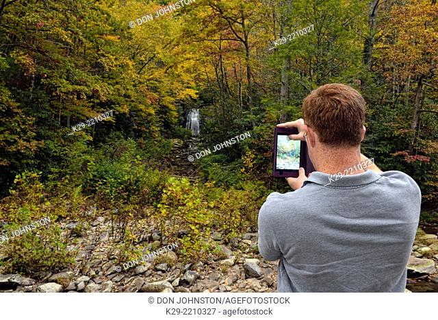 Tourist photographing Meigs Falls in autumn, using a tablet, Great Smoky Mountains NP, Tennessee, USA