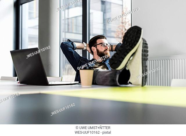 Young casual businessman sitting in office with feet up and a cup of coffee