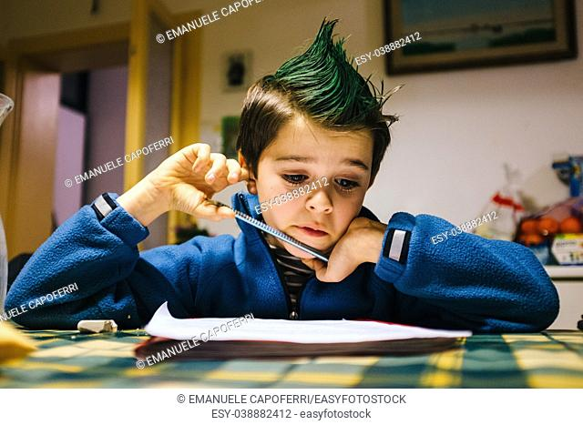 portrait of 9 year old boy at home with green colored hair crest performing school homework
