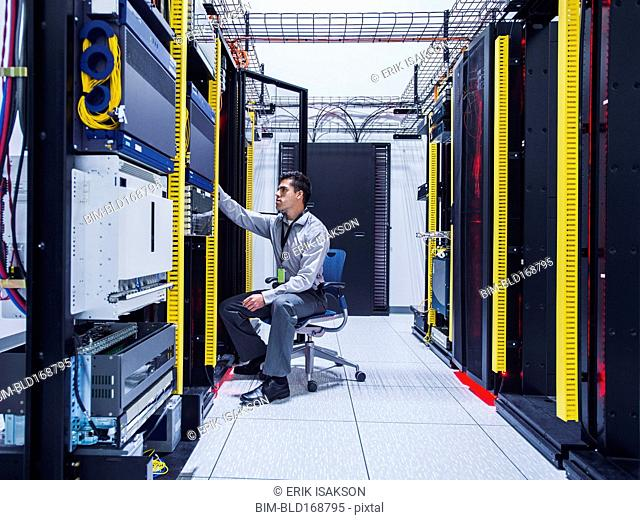 Hispanic technician examining computer in server room