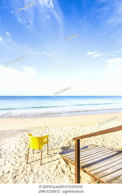wooden footbridge and yellow plastic chair on deserted beach, praia da rocha, portimao, algarve, portugal