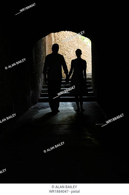 Italy, Ravello, Mature couple walking in dark archway