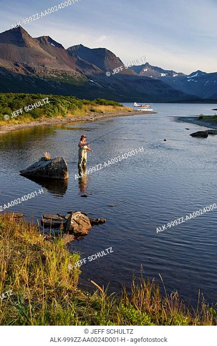 Angler fly fishing in Bristol Bay in the evening near Crystal Creek Lodge with a floatplane moored in the background, King Salmon, Southwest Alaska, Summer