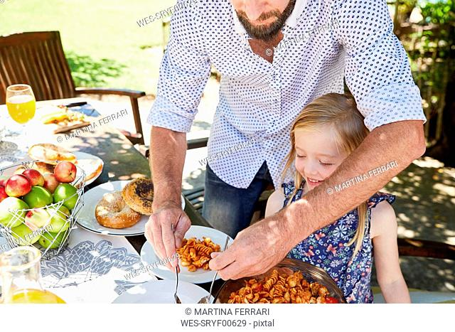 Father dishing up pasta for daughter at garden table