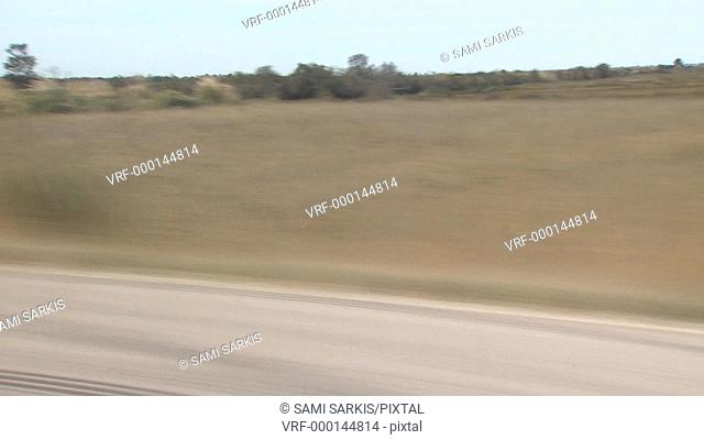 Blurred road and countryside view from a speeding car, Camargue, France