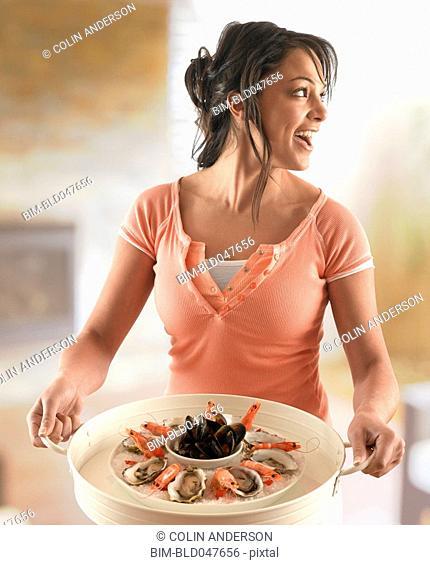 Hispanic woman carrying platter of seafood