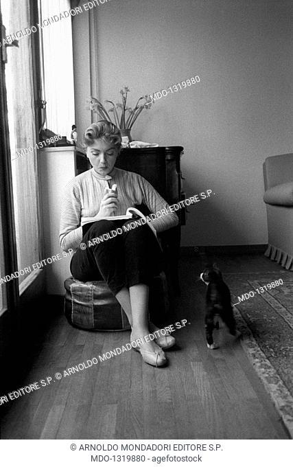 Sylvia Koscina eating. Croatian-born Italian actress Sylvia Koscina (Sylva Koskinon) reading and eating. 1950s