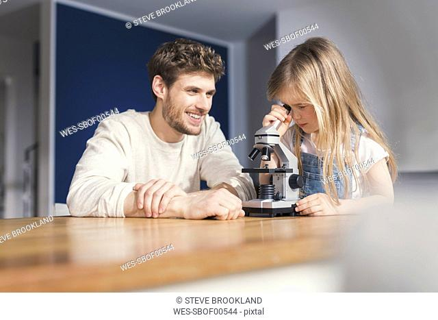 Father watching daughter use a microscope, smiling proudly