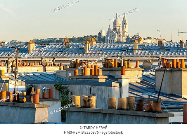 France, Paris, Le Sacre Coeur in the distance on the hill of Montmartre, emerges above the roofs and chimneys North of the city (aerial view)