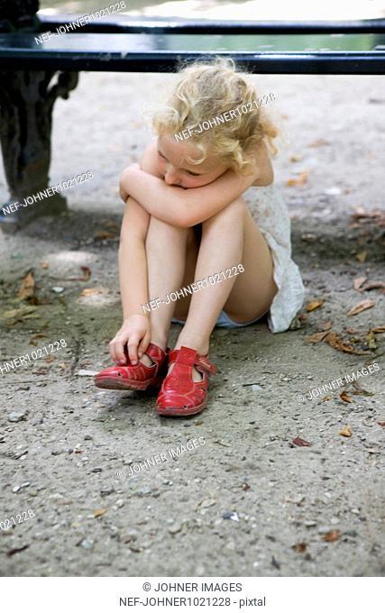 Girl sitting on ground alone