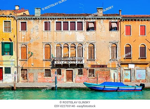 Typical old colorful brick house, wooden shutters on windows and small canal in Venice, Italy