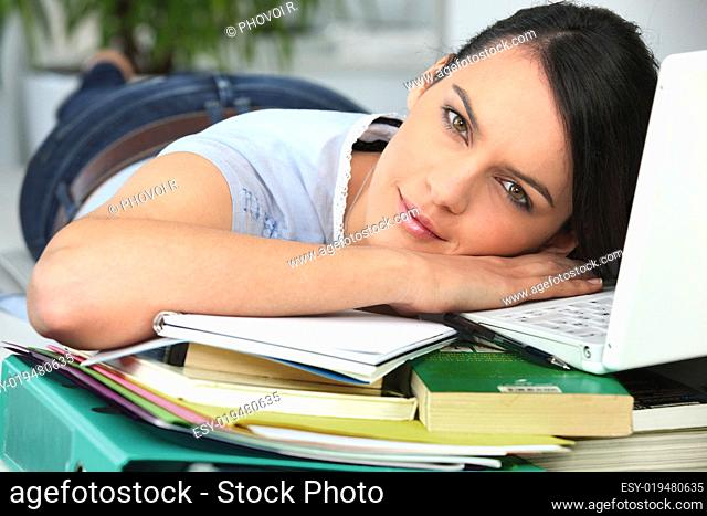 young brunette lying flat near PC with books and files