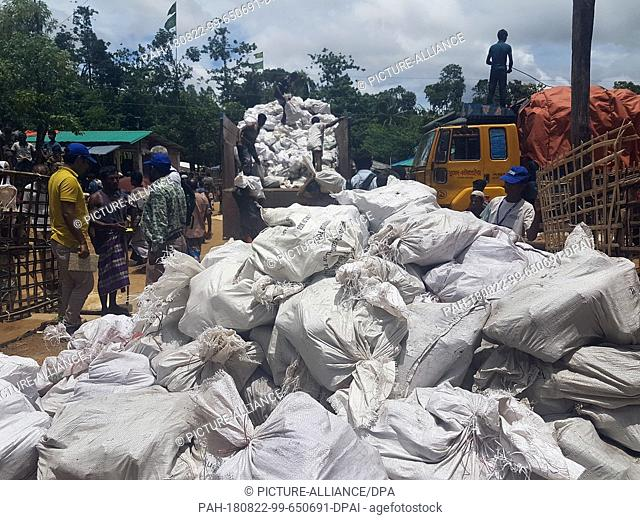 14 August 2018, Bangladesh, Cox's Bazar: Bags weighing 18.5 kilograms each with fuel rods made of compressed rice husks are unloaded from a truck for cooking at...