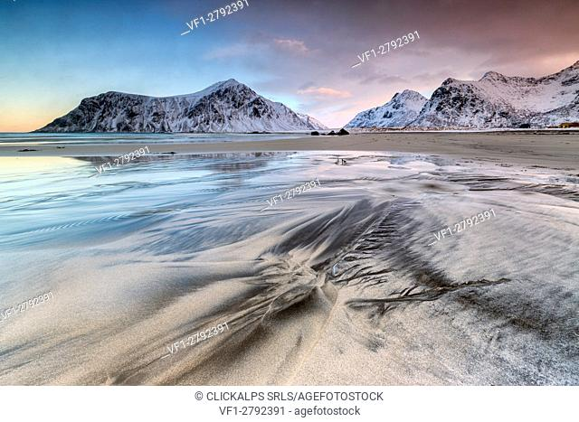 Pink sky on the surreal Skagsanden beach surrounded by snow covered mountains. Lofoten Islands Northern Norway Europe