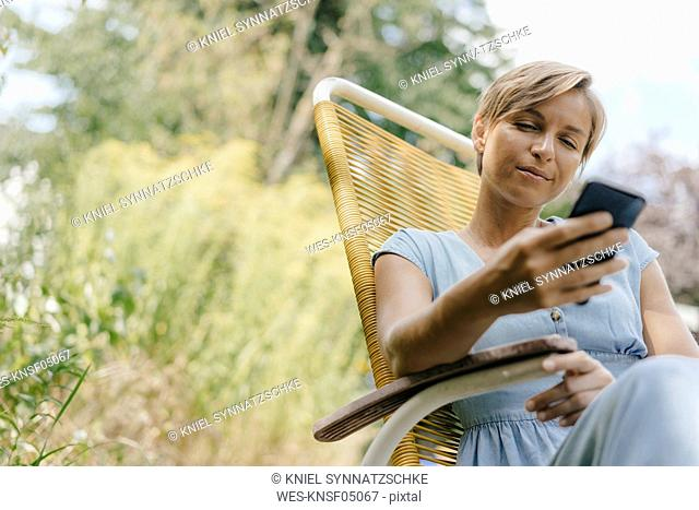 Woman sitting in garden on chair using cell phone