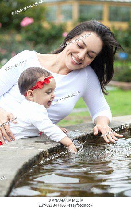 Baby girl and her mom playing with water