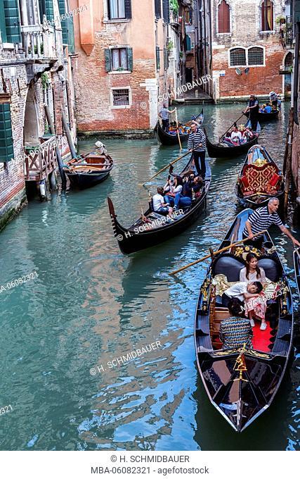 Tourists go with gondolas on canal, Venice, Italy