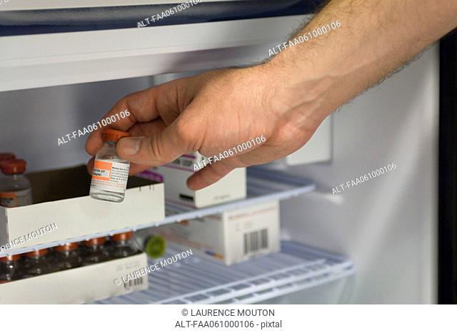 Healthcare professional removing vial of medication from refrigerator