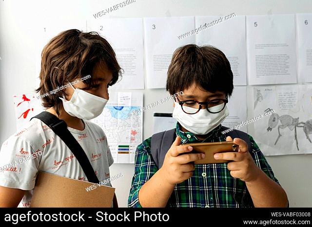 Boy wearing mask looking at friend using smart phone while standing against wall in school