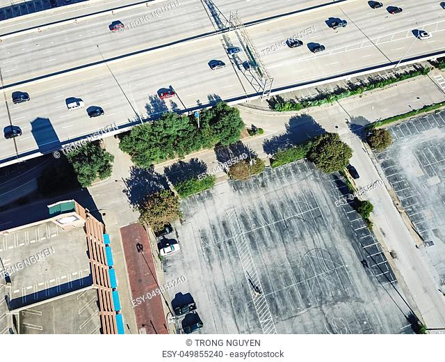 Top view multistory garage near parking lots with many vacant spaces at rooftop and outdoor. Public infrastructure in downtown Dallas, Texas