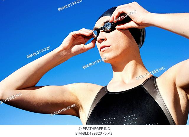 Competitive swimmer adjusting goggles