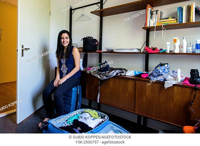 Tilburg, Netherlands. Young South-American brunette student, packing her bags prior to leaving her present Airbnb guest-room for a new accommodation