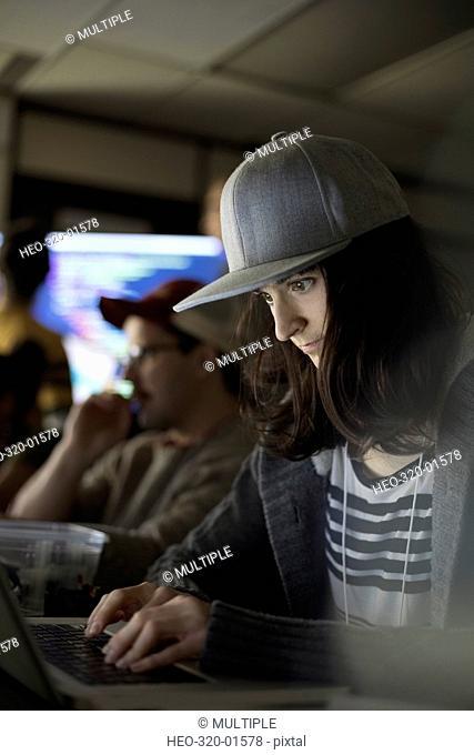 Focused female hacker wearing baseball cap working hackathon at laptop in dark office
