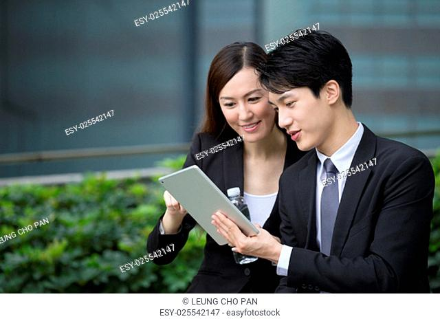 Business man and woman discuss about the financial plan on digital tablet
