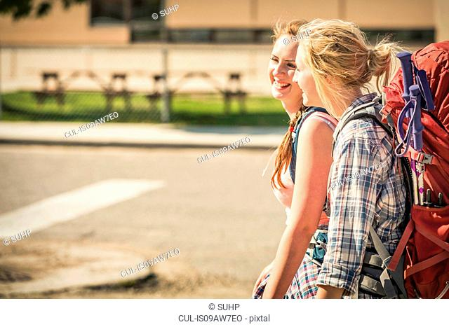 Teenage girl and young female hiker hiking on road, Red Lodge, Montana, USA