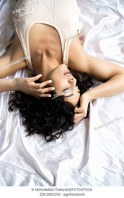 Beautiful young woman laying down in bed hands on head