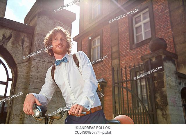 Young man outdoors, riding bike, wearing shirt and bow tie