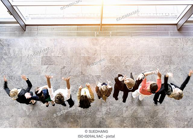 Overhead view of business team in a row jumping for joy
