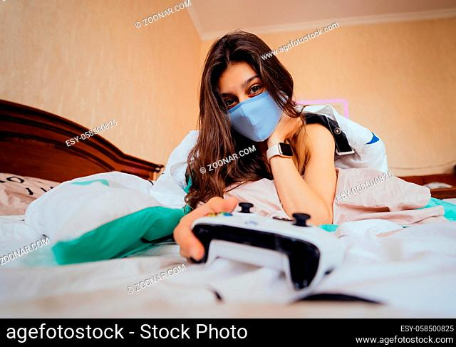 Funny girl in casual clothing lying in bed and playing video game, holding controller in hands
