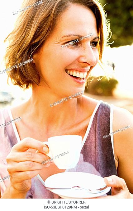 Woman having espresso outdoors