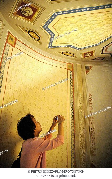 Vignola Modena, Italy, an Asian tourist taking a photo at Palazzo Barozzi's winding staircase