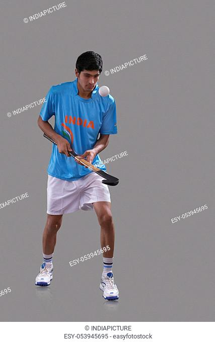 Young Indian sports man practicing hockey isolated over gray background