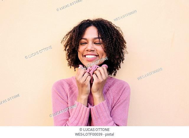 Portrait of happy young woman wearing pink pullover