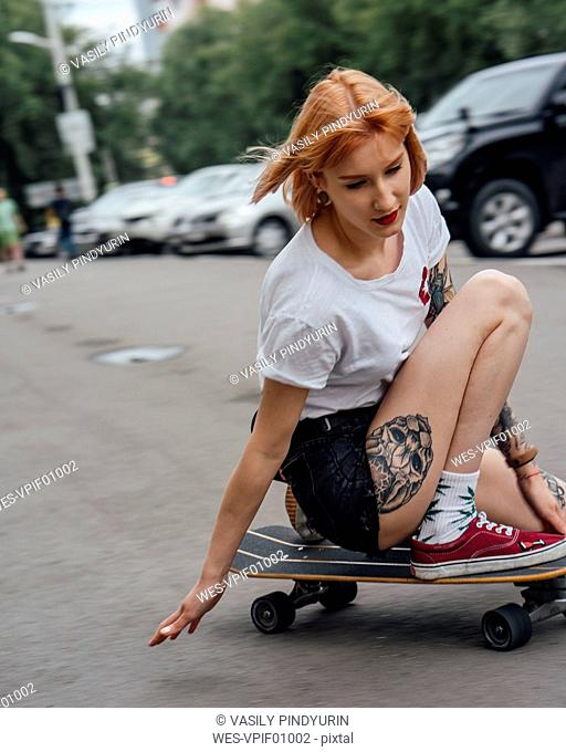 Young woman riding on carver skateboard on a street