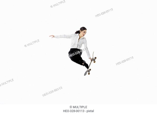 Businesswoman with skateboard jumping against white background